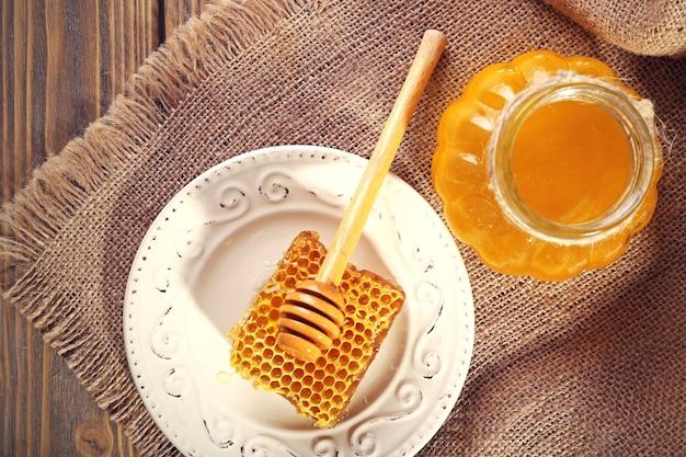 Горшок меда и сот с ковшом на деревянной поверхности