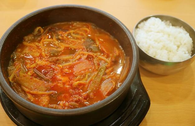 キムチチゲまたは韓国の辛くて辛いキムチチゲの鍋に木製のテーブルにご飯を添えて