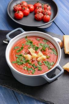 木製のテーブルにおいしいトマトクリームスープの鍋