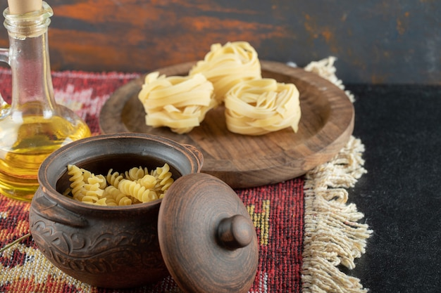 A pot of raw spiral macaroni with uncooked rolled pasta on wooden board