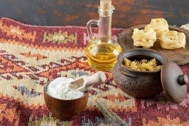 Una pentola di maccheroni a spirale crudi con pasta arrotolata cruda su tavola di legno