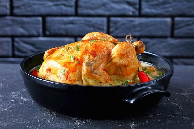 Жареный кокосовый цыпленок с картофелем в черной керамической голландской печи на бетонном столе с кирпичной стеной у стола, горизонтальный вид сверху, крупный план