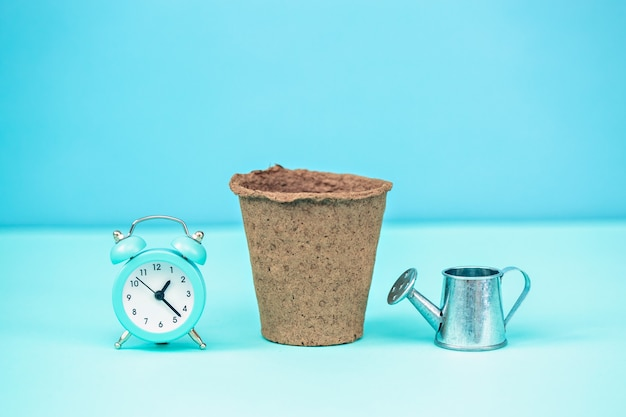 A pot for seedlings on a blue background with an alarm clock and a watering can.