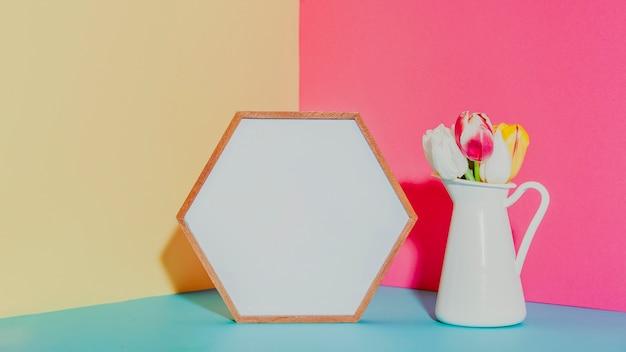 Vaso con fiori vicino cornice esagonale