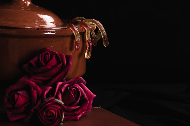 Pot with jelly and roses on black background