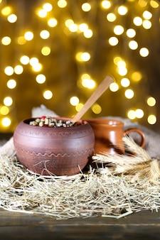 Kutiaのポット-明るい背景に、木製のテーブルの上に、ウクライナ、ベラルーシ、ポーランドの伝統的なクリスマスの甘い食事