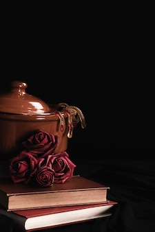 Pot with roses and jelly on black background