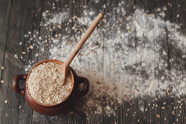 Pot with a spoon full of cereals and on rustic background. top view