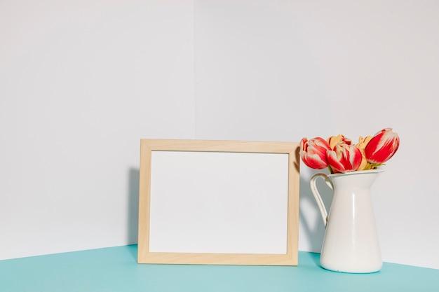 Pentola con tulipani vicino alla cornice vuota