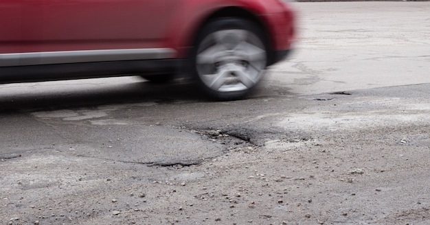 車は道路のpot穴を一周します。冬の後壊れたアスファルト。