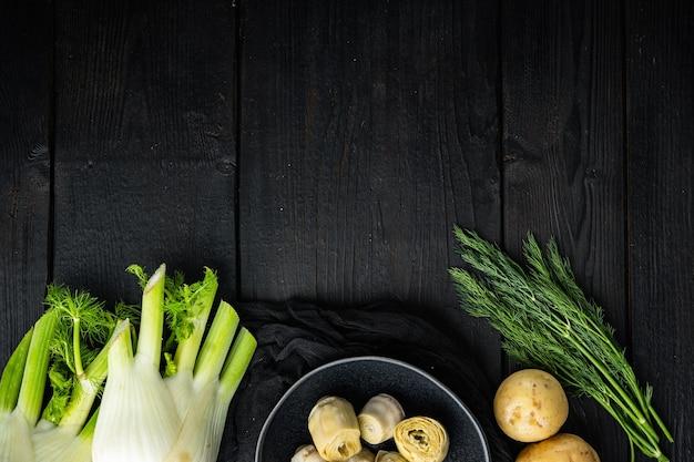 Картофель и артишок аль-форно, на черном деревянном столе, вид сверху с пространством для текста