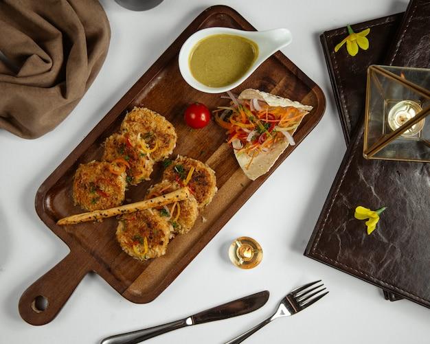 Картофельные шарики с овощами и соусом на деревянной доске