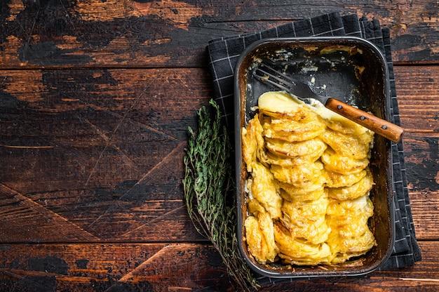 Картофельная запеканка гратен дофинуа в форме для запекания. темный деревянный фон. вид сверху. скопируйте пространство.