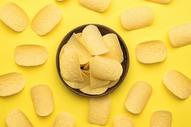 노란색 배경에 감자 칩과 점토 그릇. 인기있는 감자 요리. 플랫 레이.