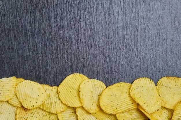 Картофельные чипсы выкладываются на грифельные тарелки. вид сверху с копией пространства.