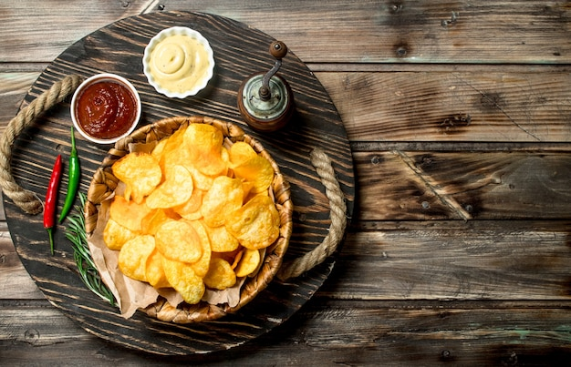Potato chips in a basket with different sauces. on a wooden table.