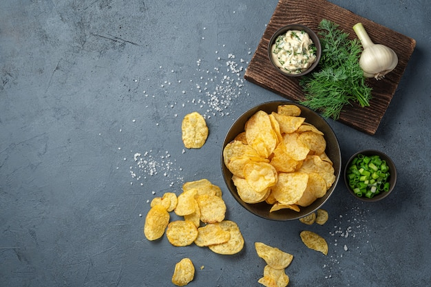 Potato chips, beer appetizer on a dark gray background. top view, copy space.