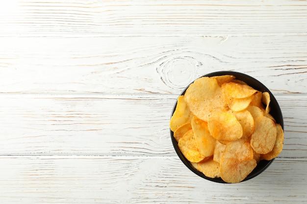 Картофельные чипсы. закуски к пиву на белой древесине, космосе для текста. вид сверху