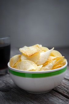 Potato chips in bowl with cola on wooden table background.