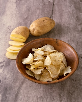 Potato chips on a bowl with raw potato