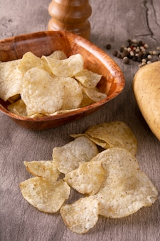 Potato chips on a bowl and over wood background with pepper and grinder