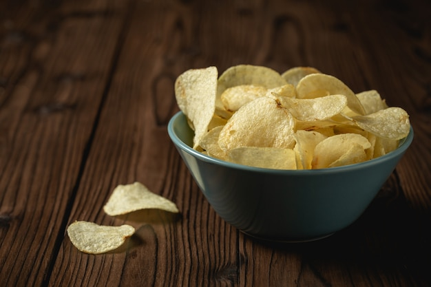 Potato chips in bowl on a wooden table.