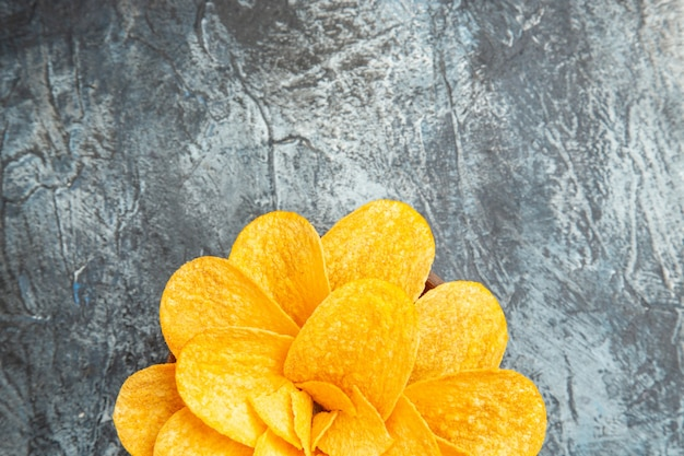 Potato chips decorated like flower shaped in a brown bowl on gray table