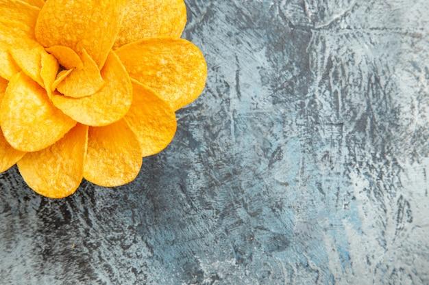 灰色のテーブルの上の茶色のボウルに花の形をしたポテトチップス