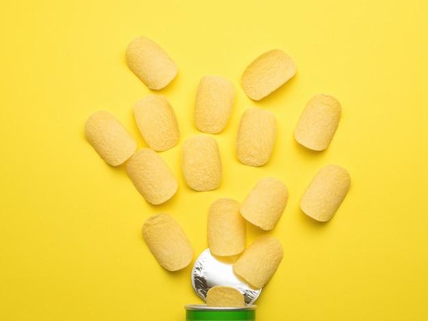 감자 칩은 노란색 배경에 있는 항아리에서 떨어집니다. 인기있는 감자 요리. 플랫 레이.