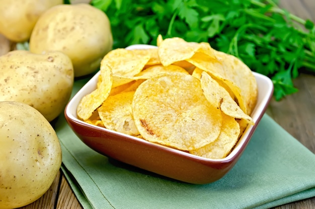 ナプキン、新鮮なジャガイモ、木の板の背景にパセリの粘土ボウルのポテトチップス