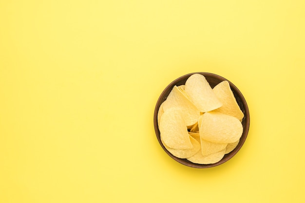 노란색 배경에 점토 그릇에 감자 칩. 플랫 레이.
