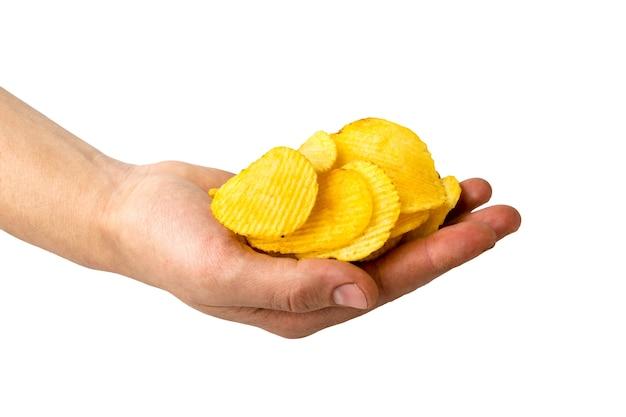 Картофельные чипсы в мужской руке на белом