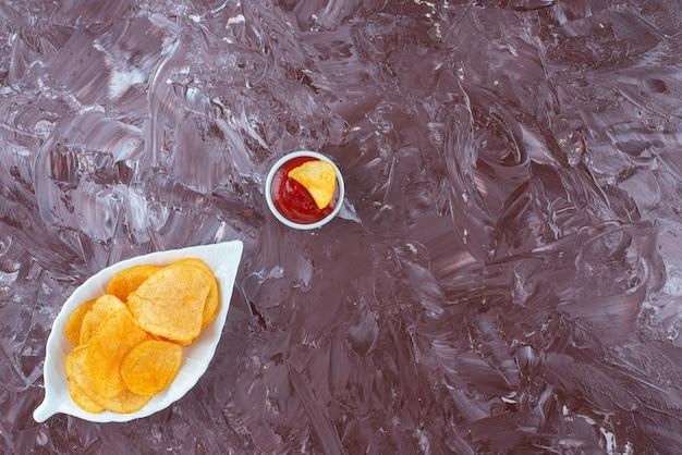 대리석 테이블에 그릇에 케첩 옆 접시에 감자 칩.