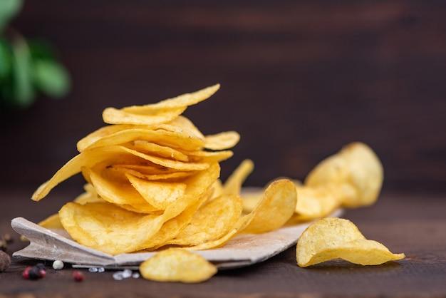 Картофельные чипсы в миске на дереве