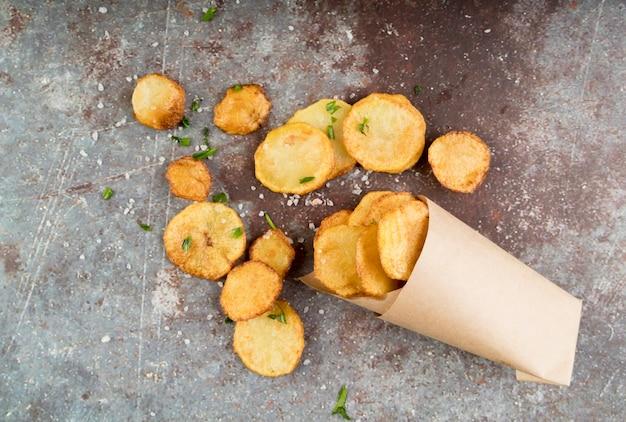 Картофельные чипсы в бумажном пакете на цементном фоне