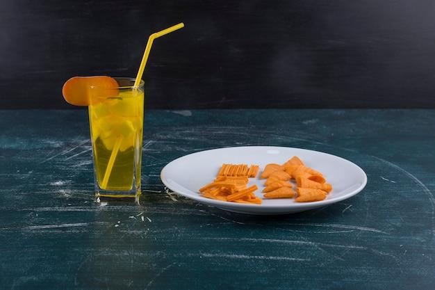 Картофельные чипсы в томатном соусе в белой тарелке со стаканом сока