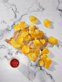 Potato chips and ketchup on a marble table - flat lay