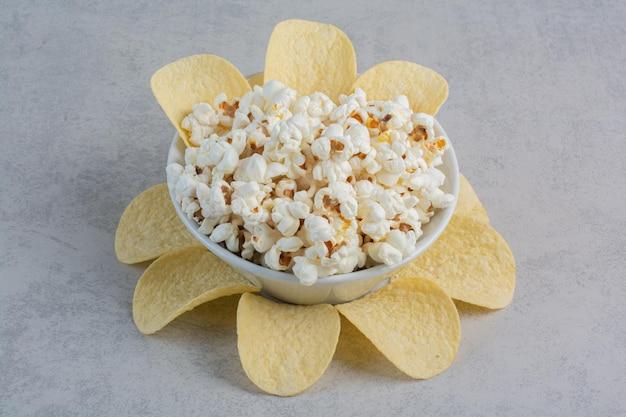 Patatine fritte allineate attorno a un piatto di popcorn su una superficie di marmo