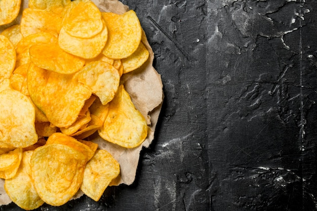 Potato chips on old paper on rustic table.