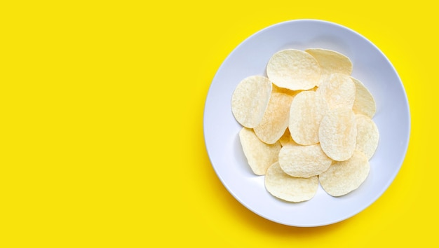 黄色の背景にポテトチップス。上面図