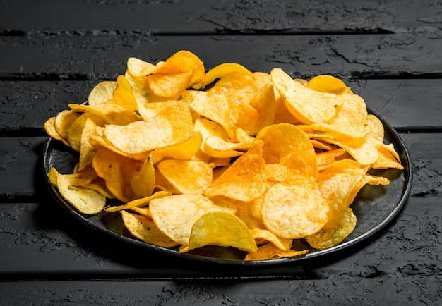 Potato chips on the plate. on black rustic table.