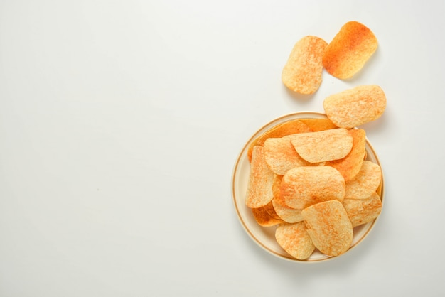 Potato chips in a plate isolated on a white background