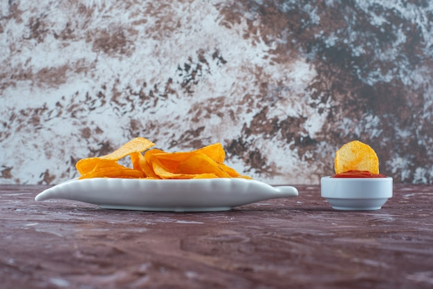 Potato chips in a plate next to ketchup in a bowl , on the marble table.