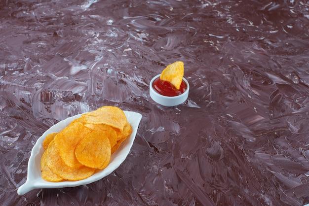 Patatine fritte in un piatto accanto al ketchup in una ciotola, sul tavolo di marmo.
