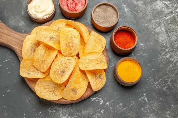 Potato chips spices and mayonnaise with ketchup on wooden cutting board on gray table