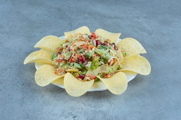 Chips di patate che circondano una porzione di insalata di formaggio e verdure su marmo.