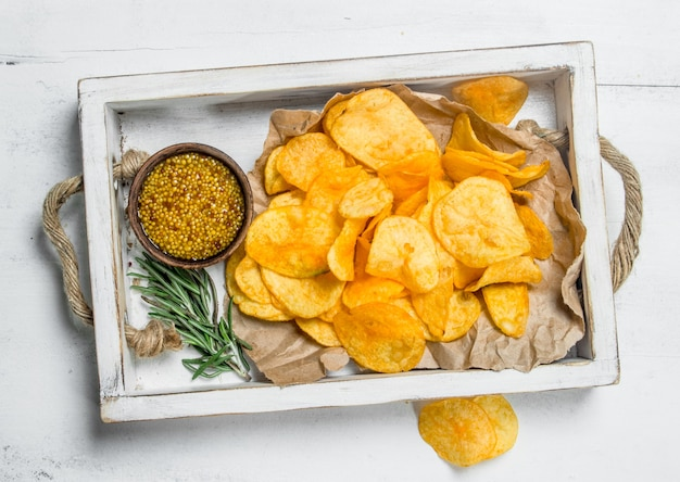 Potato chips in a white box with mustard sauce. on white rustic table.