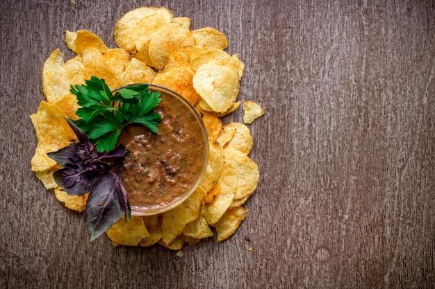 木製のテーブルにディップソースをかけたポテトチップス。木製の背景に不健康な食べ物。上面図。スペースをコピーします。フラットレイ。静物