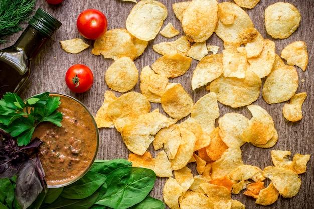 木製のテーブルにディップソースとポテトチップス木製の背景に不健康な食べ物