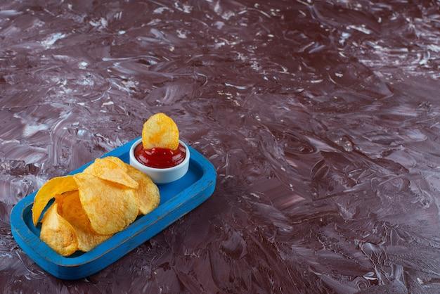 大理石のテーブルの上に、木の板にケチャップを添えたポテトチップス。